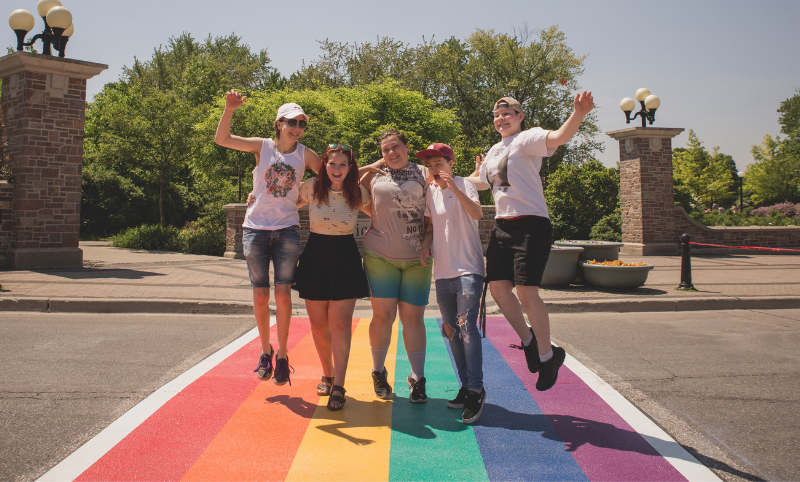 Teens on a rainbow crosswalk