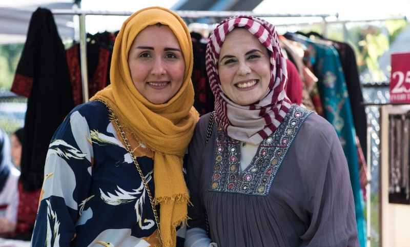 Two women celebrating Eid al-Adha at a bazaar